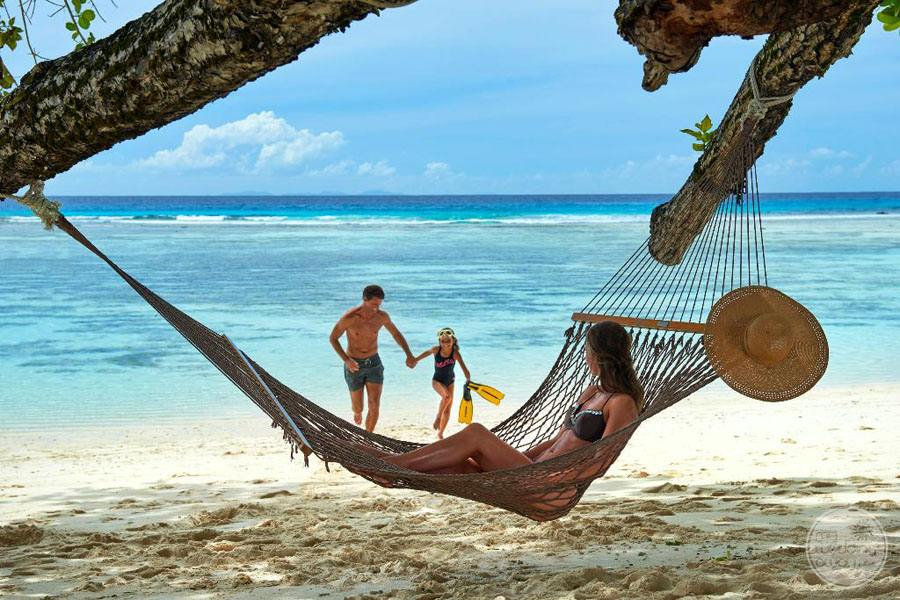 hammock on beach with family in the water