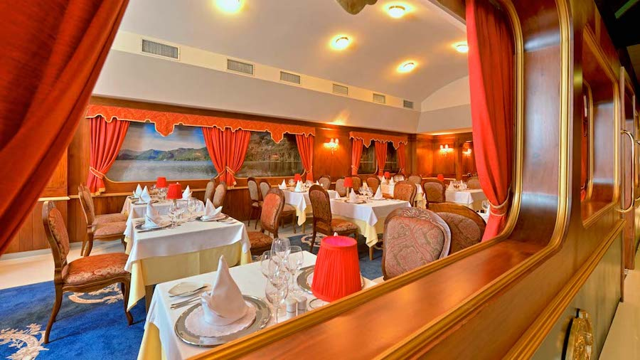 main restaurant in the evening with orange curtains white table linens and glassware and decor set up on the table