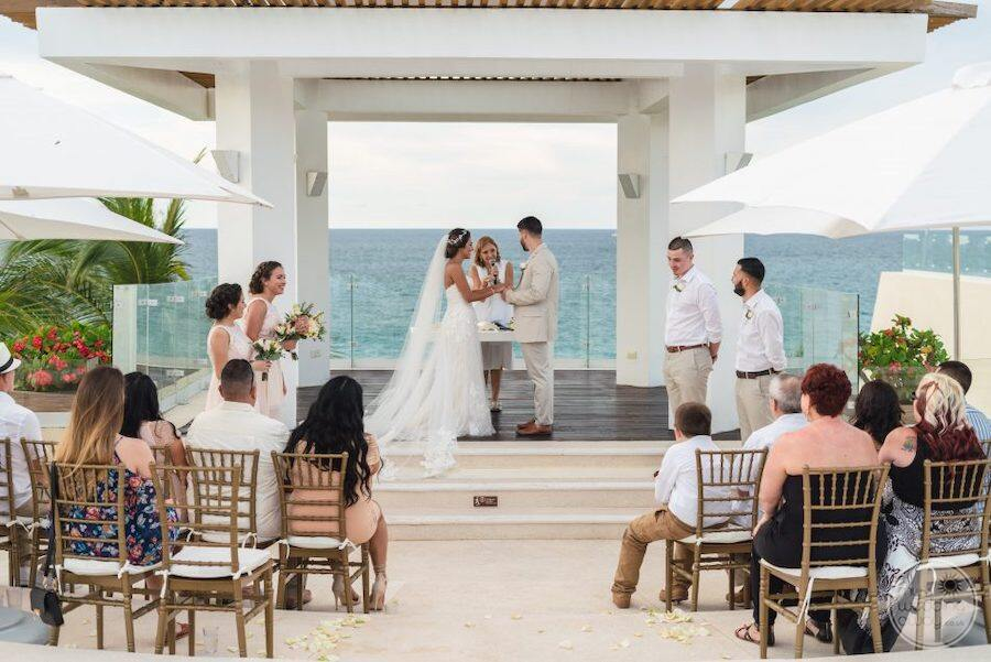 Wedding  couple celebrating there wedding vows in front of gazebo and wedding guests
