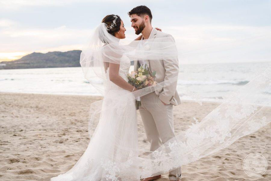 wedding couple on beach with flower bouquet embracing