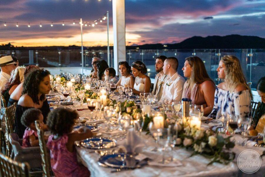 wedding reception with guests sitting at the table overlooking the ocean and mountains at sunset