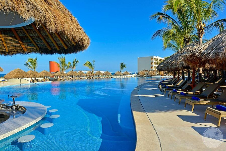 main swimming pool area with swim up bar and loungers with thatched  roof cabanas
