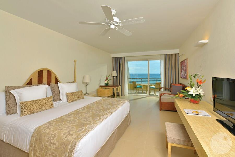 King bed ocean view room with the desk and chair and seating area and outer patio deck with a view of the ocean