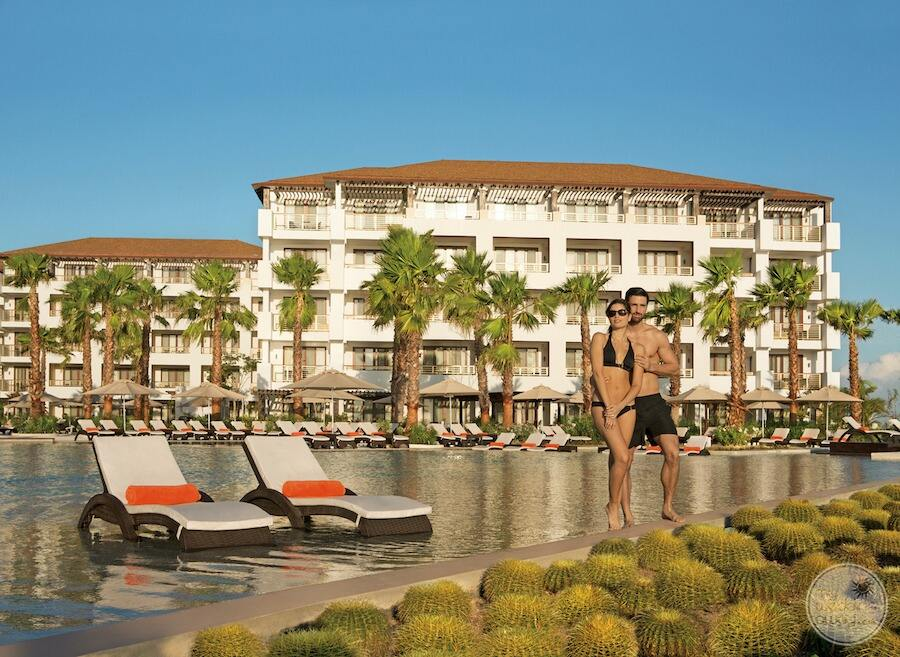 main pool area with infinity pool and room buildings in the background and couple standing by the water