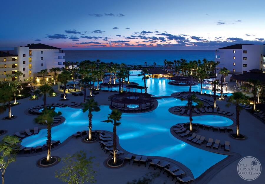 main pool is in the evening surrounded by palm trees and orange sunset