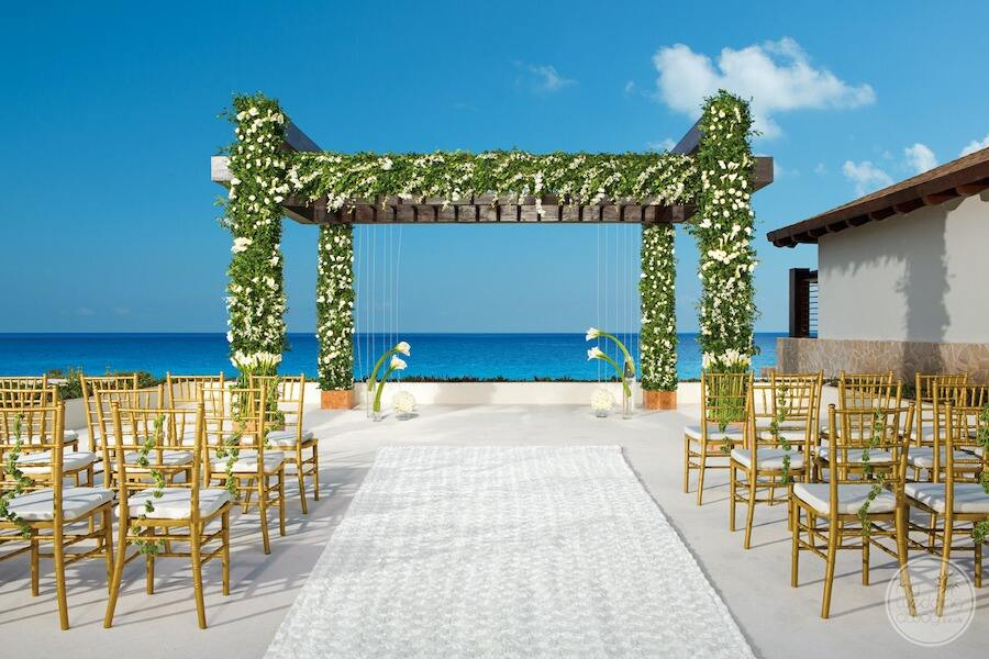 main wedding gazebo on upper terrace with beautiful flowers and shrubs and chairs along with ceremony carpet