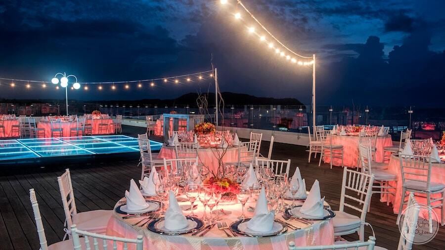 wedding reception on Ocean front terrace with beautiful lighting and pinkdecorations