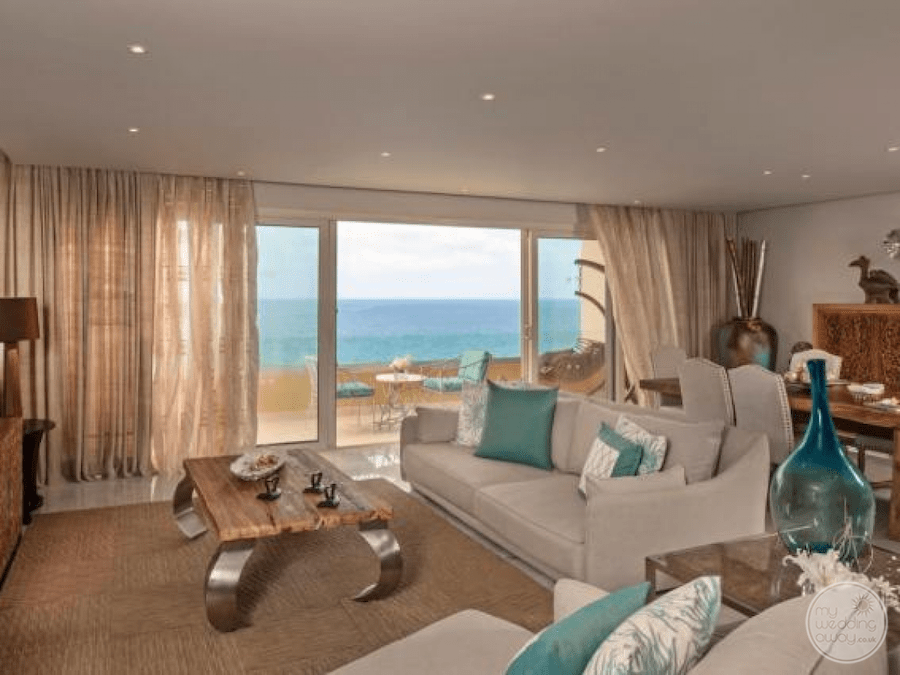 View of inside the room lounge area with table seating and deck with a view of the ocean