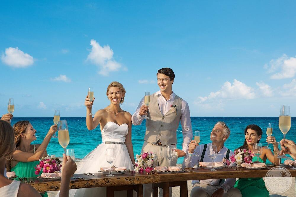 dreams-playa-mujeres-resort-and-spa-wedding-couple-on-beach-toasting-after-wedding-ceremony
