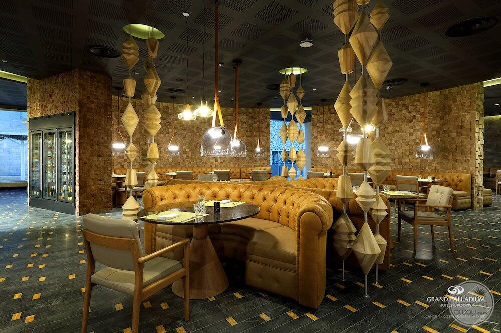 Resort steakhouse with soft yellow couches chairs and chandeliers