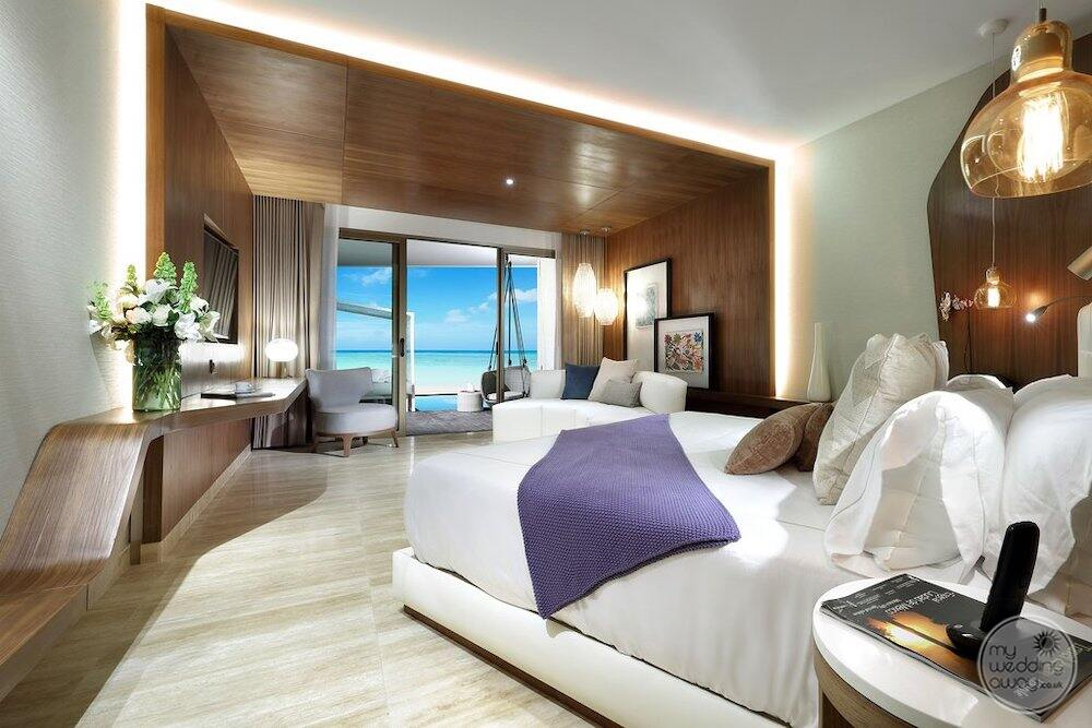 Bedroom with a white linen purple decorative blanket and view of the ocean