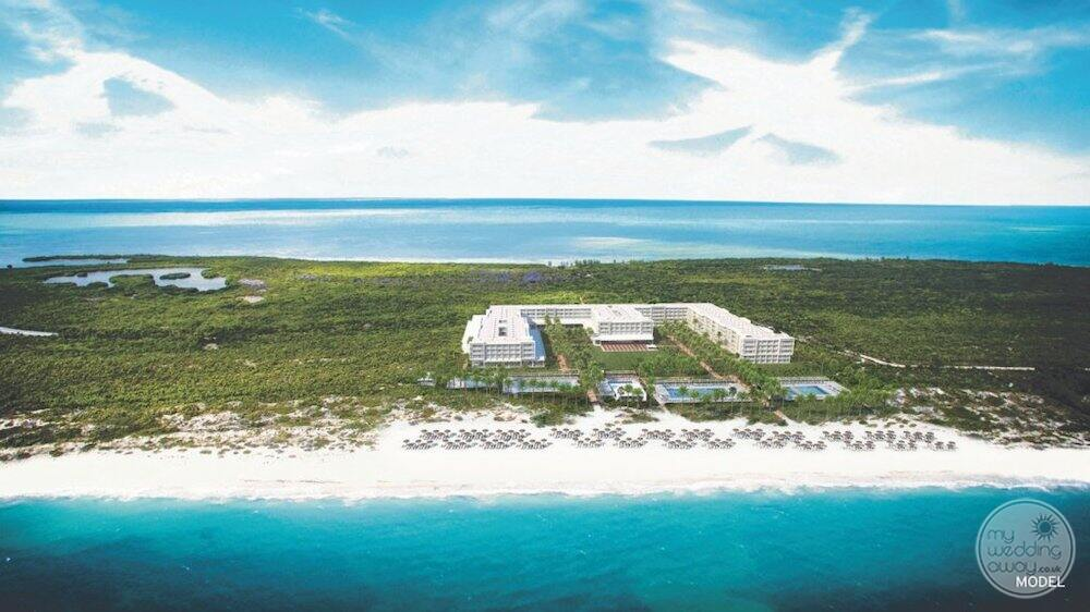Aerial view of the property with a long stretch of white sand beach and ocean