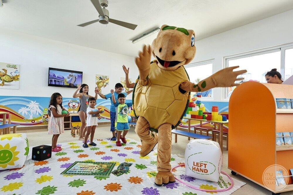 Children's play area with children dancing and singing with resort turtle