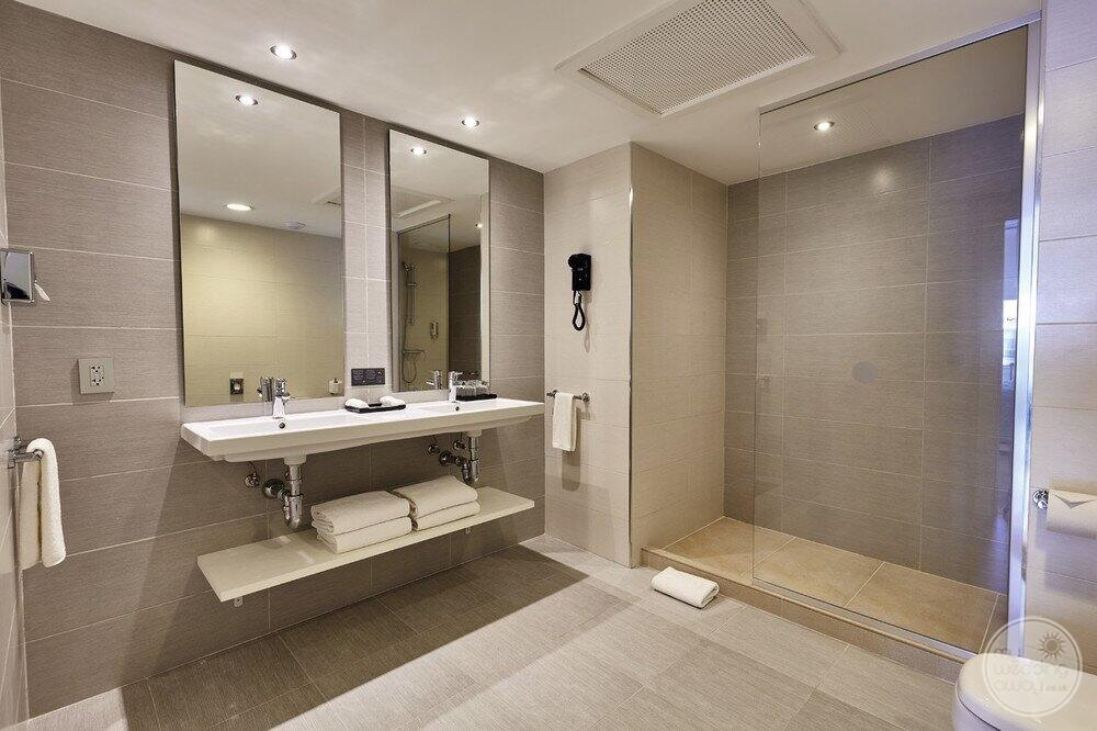 Hotel room bathroom with double vanity sinks and large shower with glass door