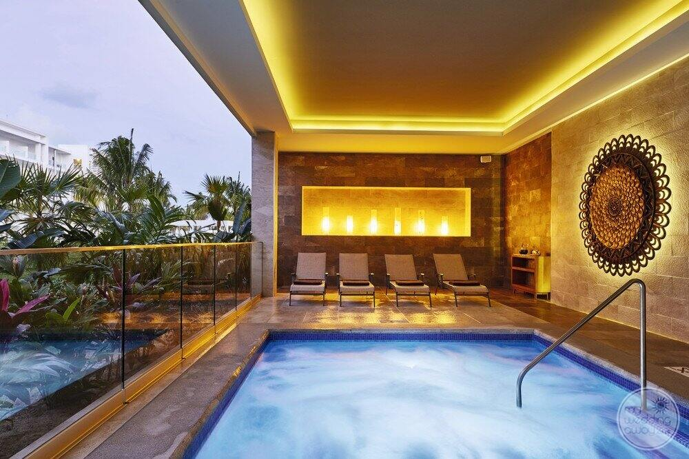 The main Jacuzzi located in the spa with seating surrounding it and artful decor
