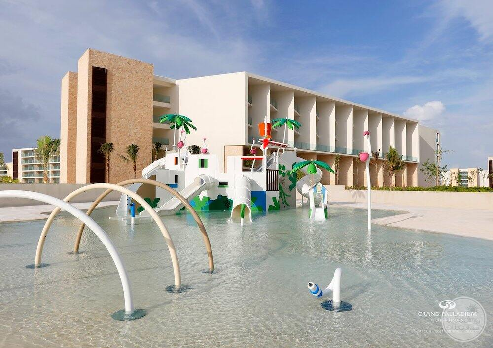 Kids water park with waterslides and shallow water play area beside room buildings