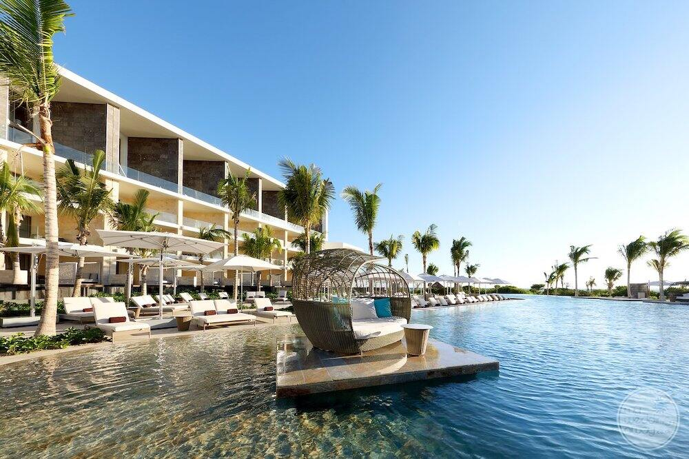 Main swimming pool area with a white lounge chairs and cabana over the water