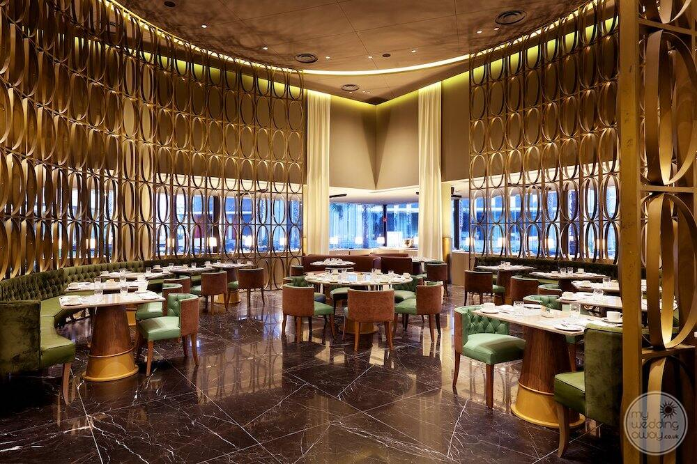 Restaurant with a beautiful brass Decour on the walls and green leather chairs