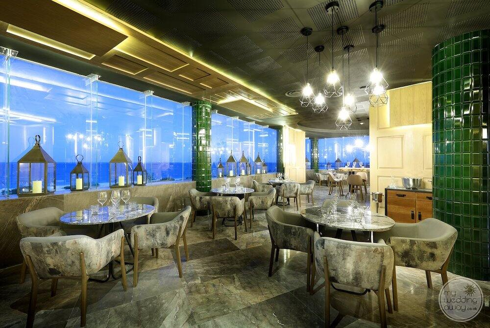Restaurant sitting with green tile walls and a view of the crew be an ocean
