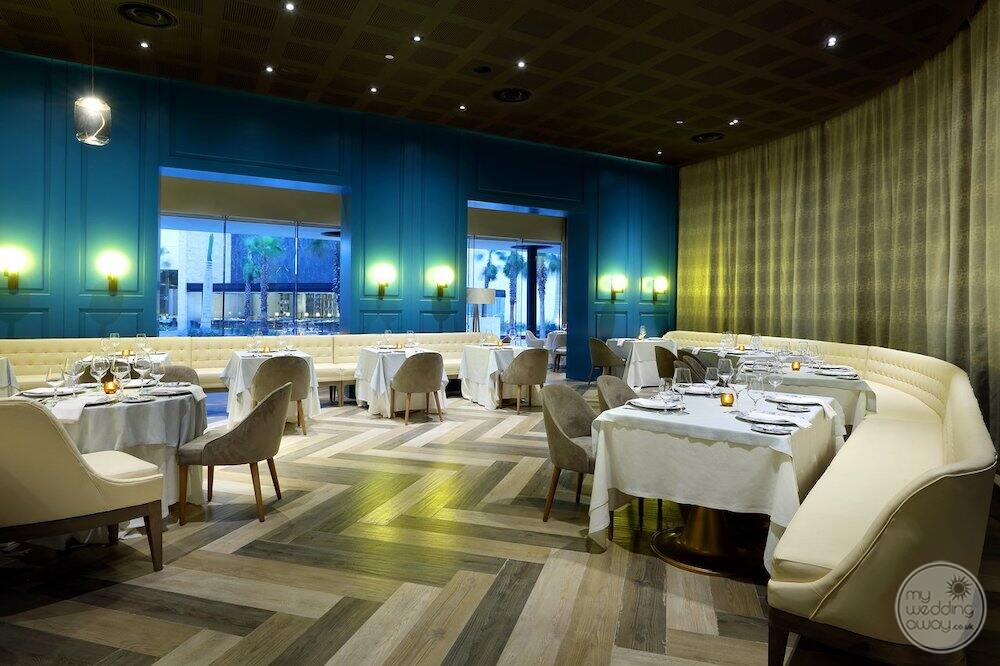 Restaurant with a white leather seating white table linen and decorated Wood flooring
