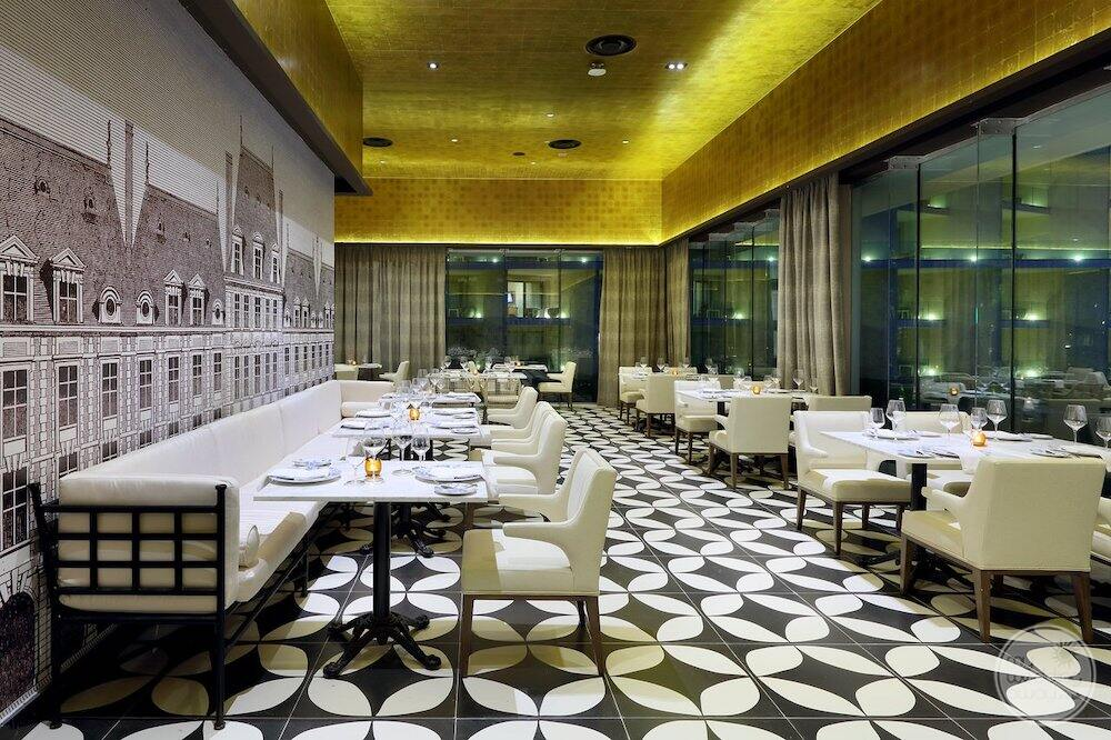 Restaurant with a white leather chairs and black and white decorative floor tiles
