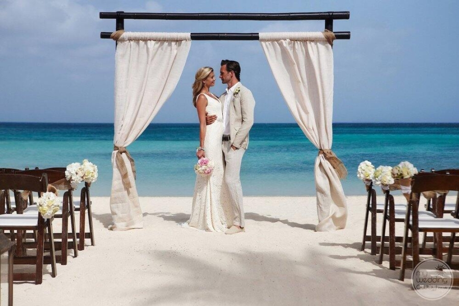 couple standing under a gazebo getting married with a wedding chairs beside the ocean