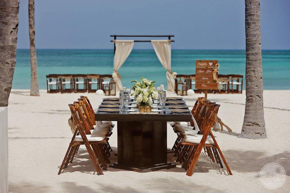 Beach wedding Sarah Moni set up with beautiful wooden chairs white gazebo and white flowers on table