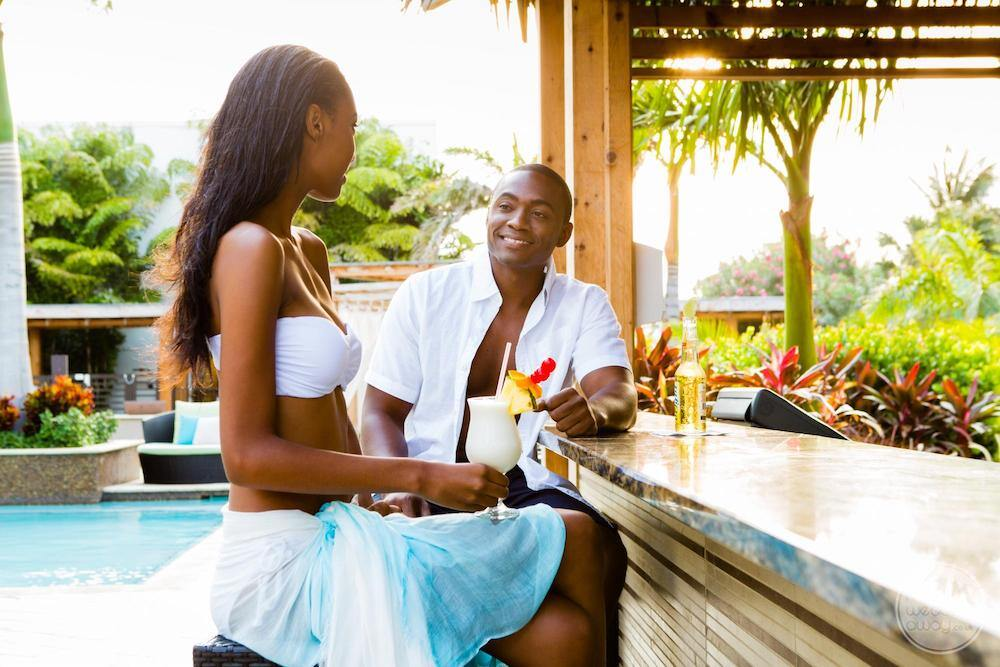 couple enjoying tropical drinks at pool bar