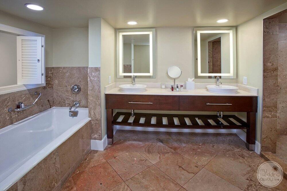 resort guest bathroom with the soaker tub double sinks and marble floors