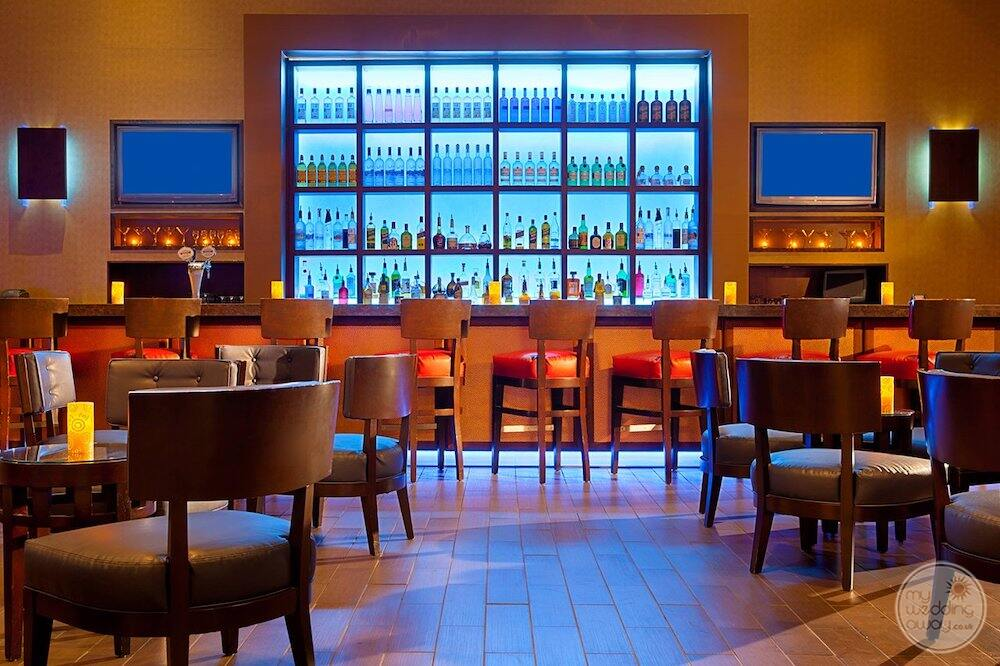 into a bar area with a beautiful Liquor and bottles on the wall with orange leather chairs