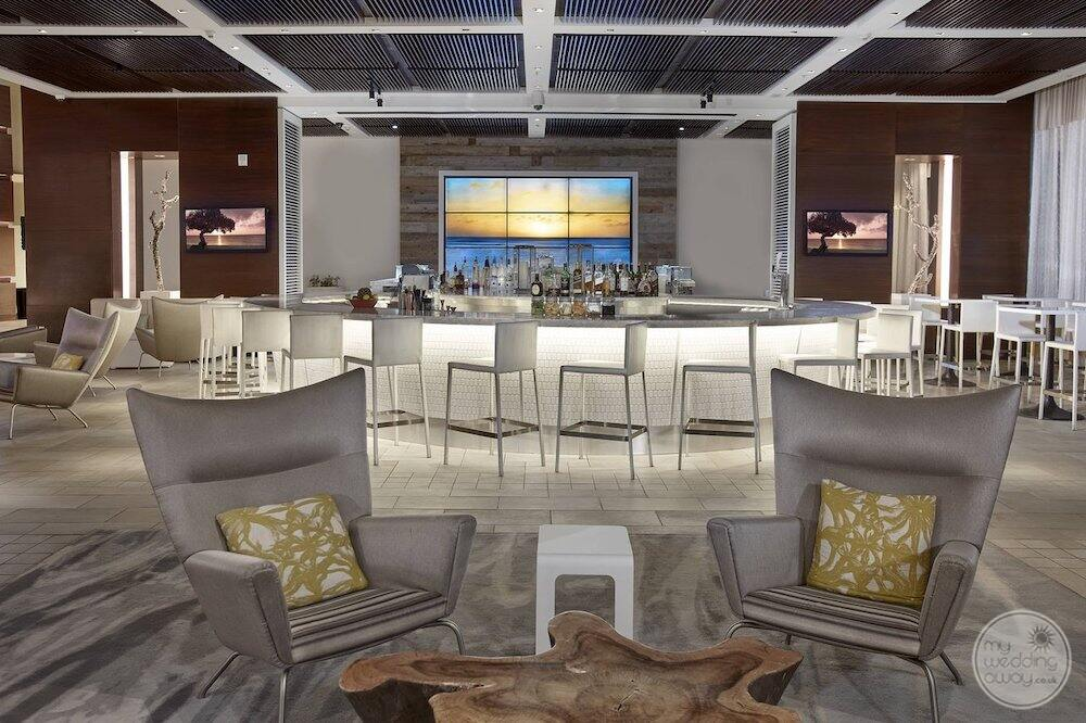 main bar area with a beautiful white ceiling Grey leather chairs in the lounge area