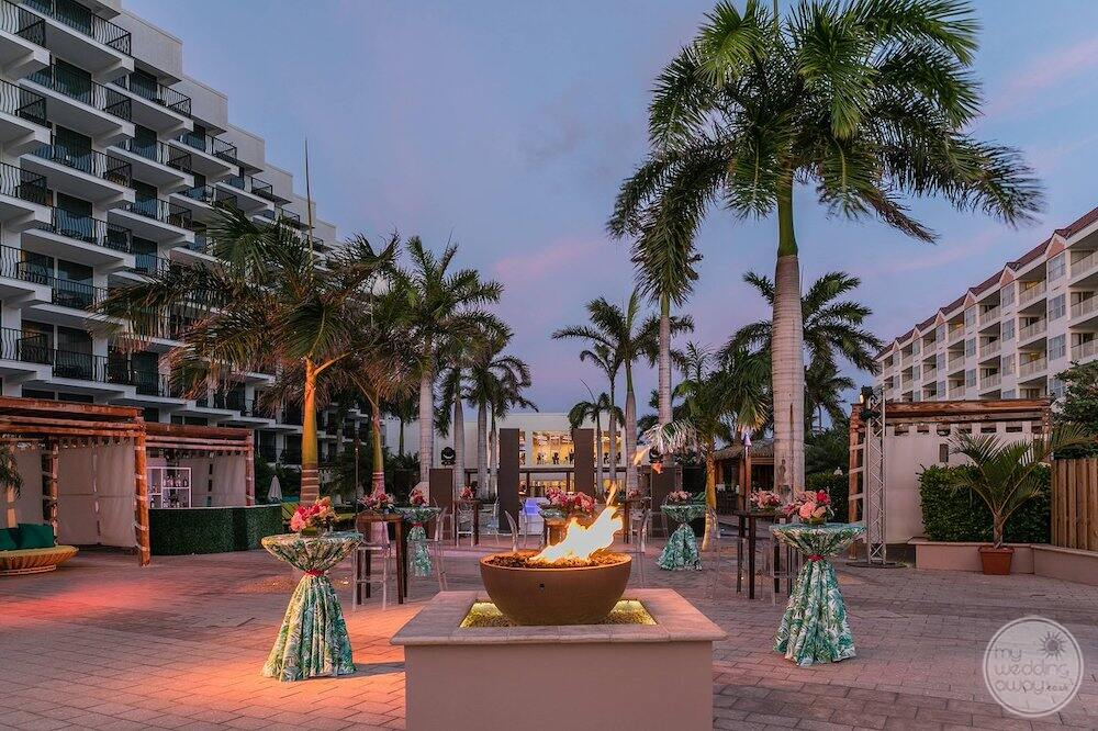 outdoor wedding venue with fire lighting and palm trees