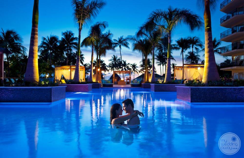 main pool at night with a couple swimming