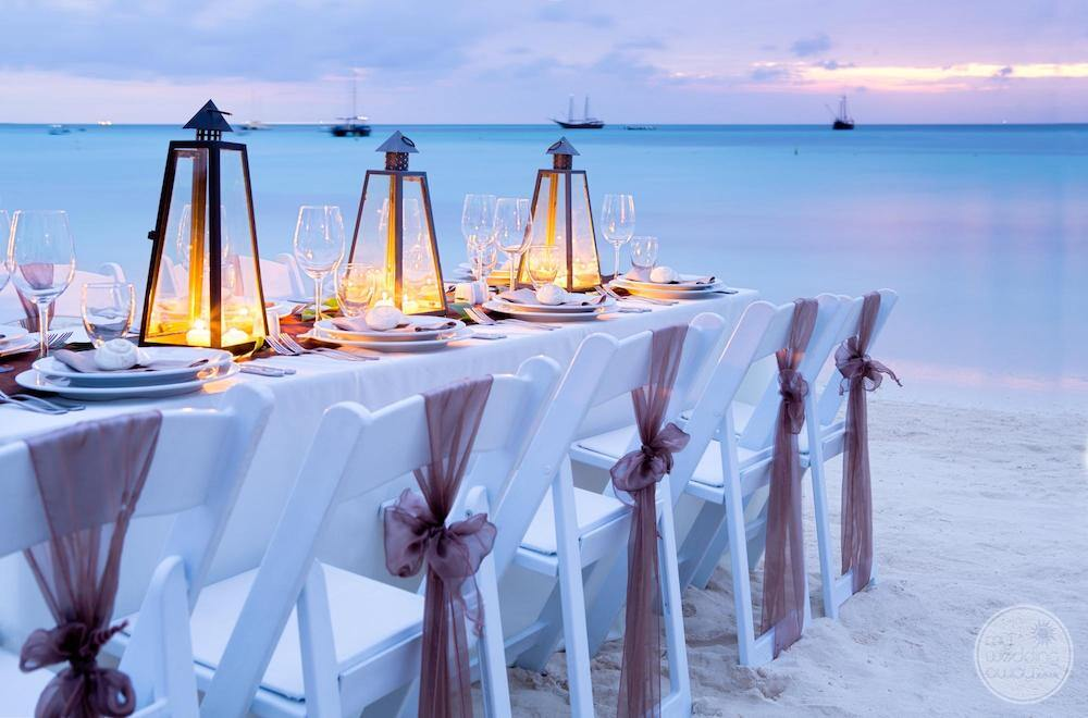 Beach at reception Sarah morning with white table linen lamps at sunset by the ocean