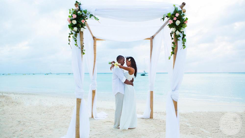 couple standing together underneath the wedding gazebo located on the beach by the ocean