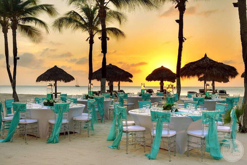 reception tables and chairs set up with blue ribbons on the beach at sunset