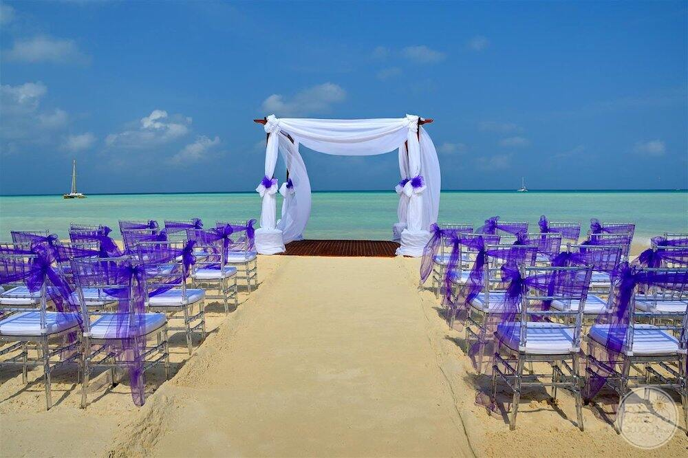 wedding ceremony set up upon the beach with purple Decour and Sarah Mauney chairs