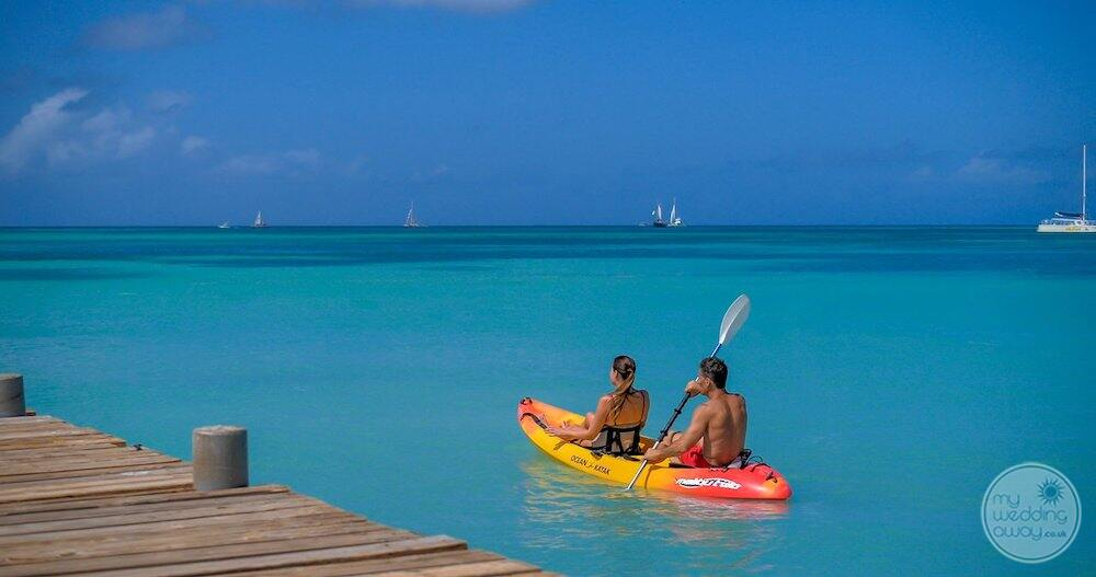 couple kayaking in the ocean by the pier after property