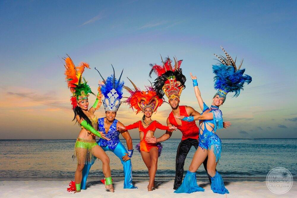 resort dancers all dressed up with a feather and headgear on the beach