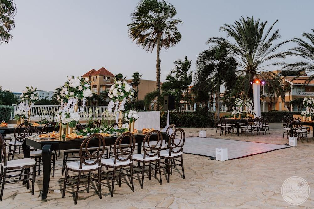Wedding reception on the terrace with white and green flowers tableside up and palm trees in the background
