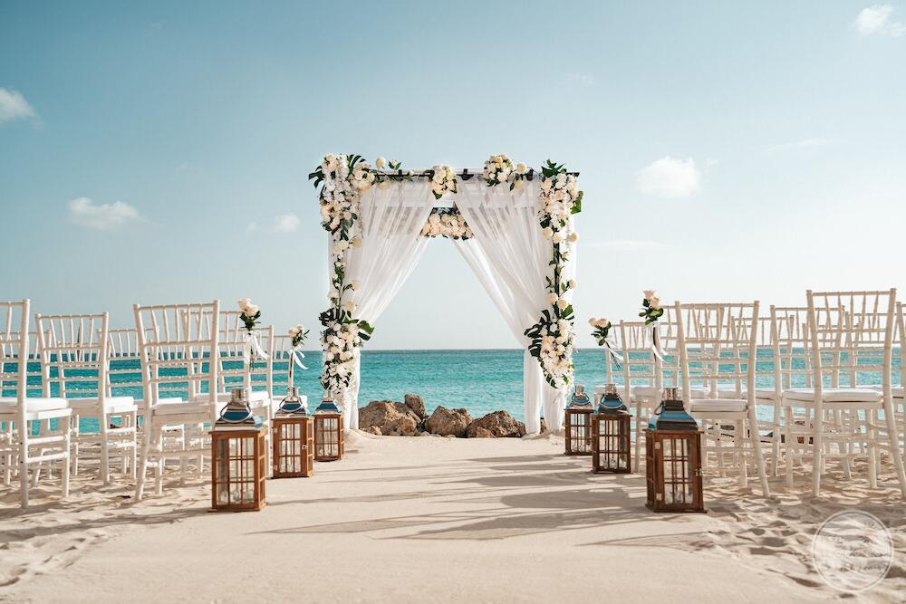 Sarah Moni set up on the beach with white flowers green florals lamps with ocean directly in the background