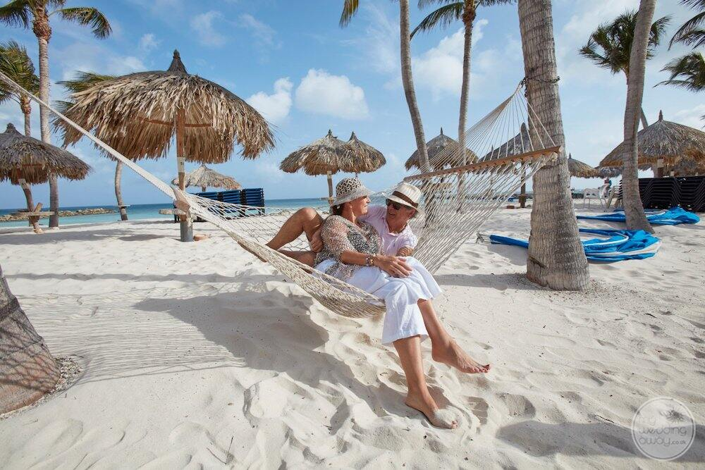 Couple on the beach in a hammock with umbrella is in the background and palm trees