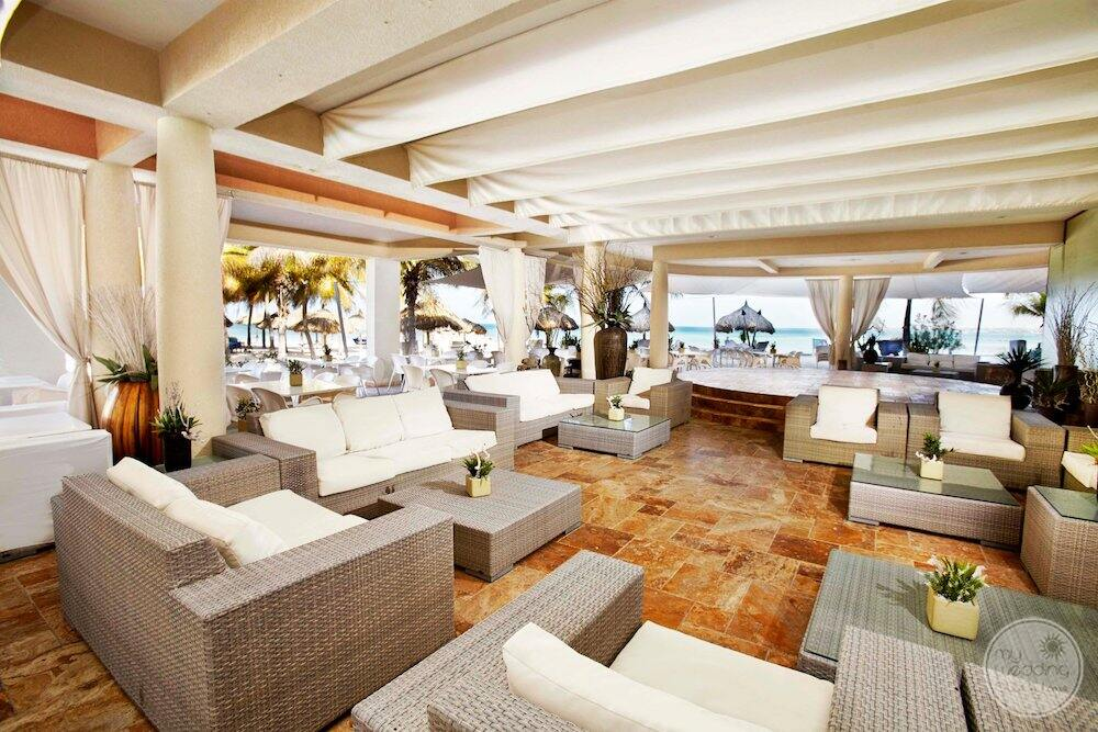 Resort lounge area with rattan couches chairs all in white with white ceiling and view of the ocean in the background