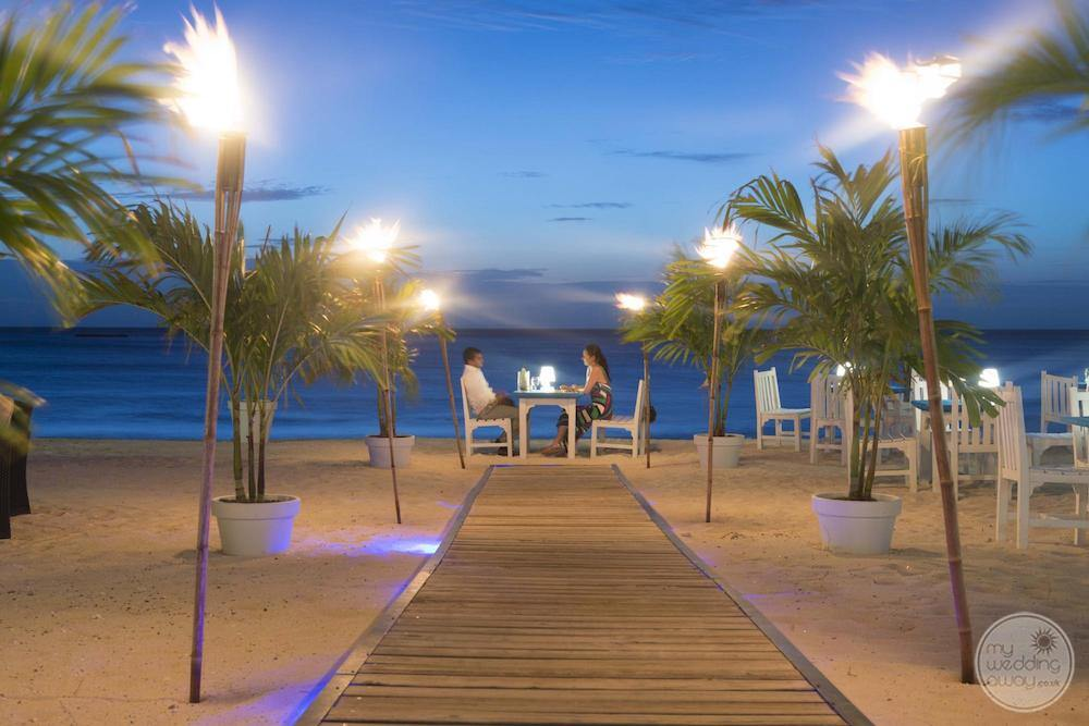 Couple enjoying a romantic dinner on the beach with tiki lights set up and wood plankwalkway