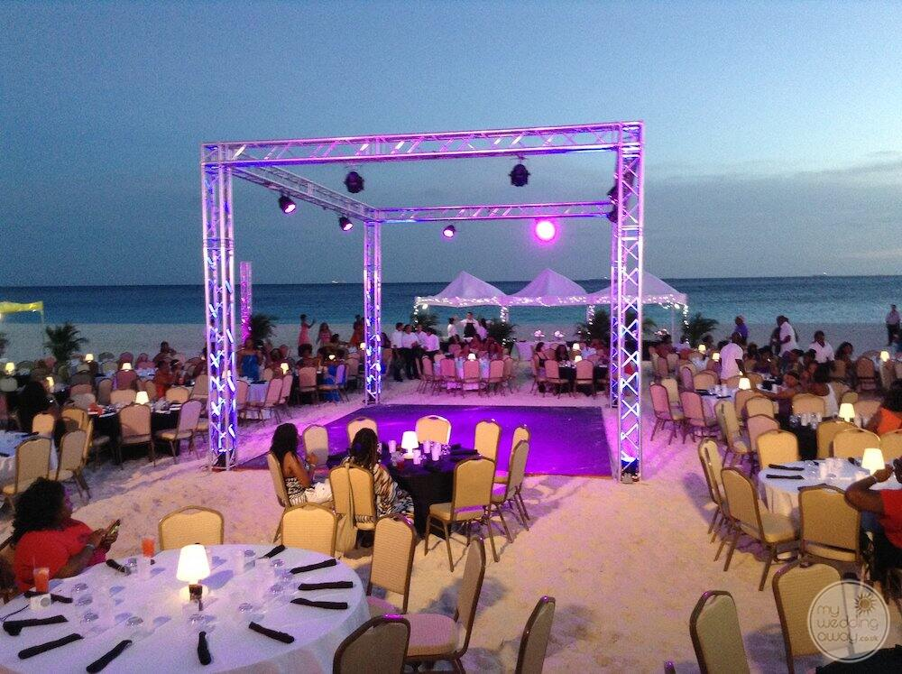 Dancefloor set up on the beach for wedding reception with purple lights