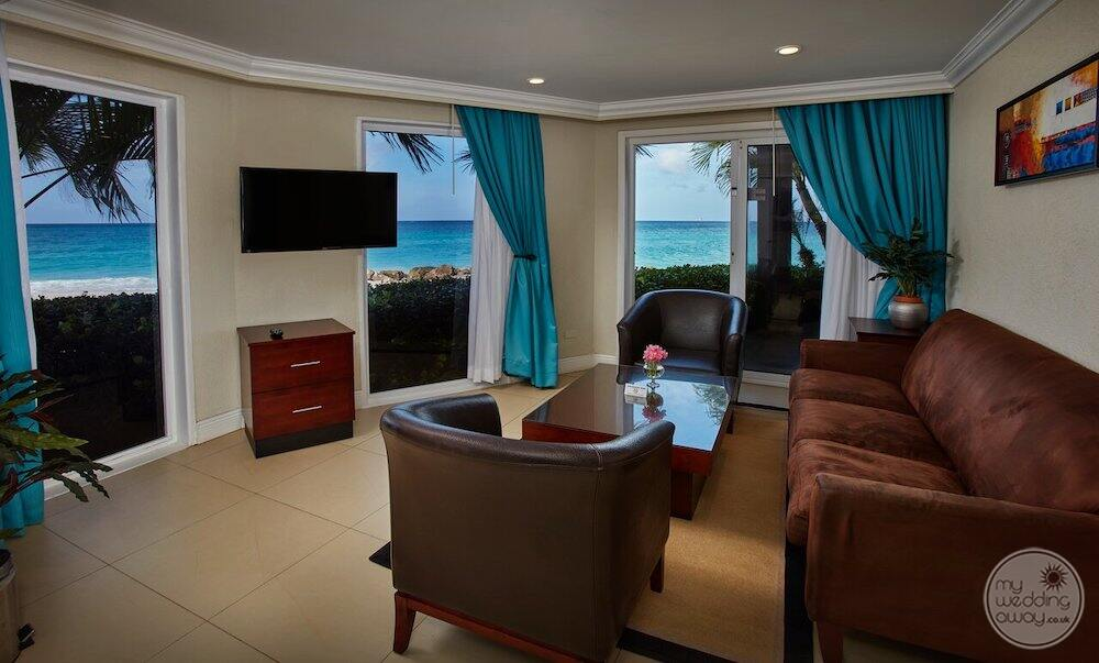 Bedroom lounge area with a brown couch brown chair blue curtains and view of the ocean