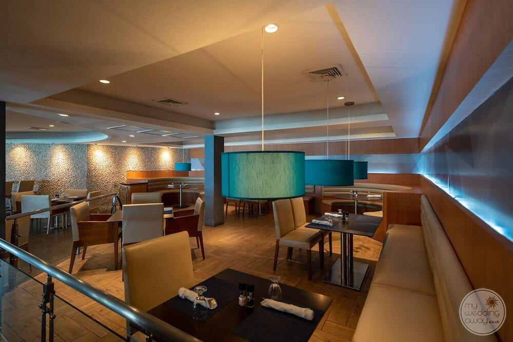 Indoor seating and restaurant area with blue lamps and leather couches and chairs