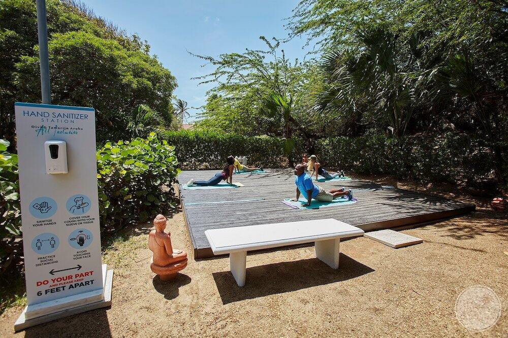 Guided yoga lessons on what playing area with surrounding trees and shrubs