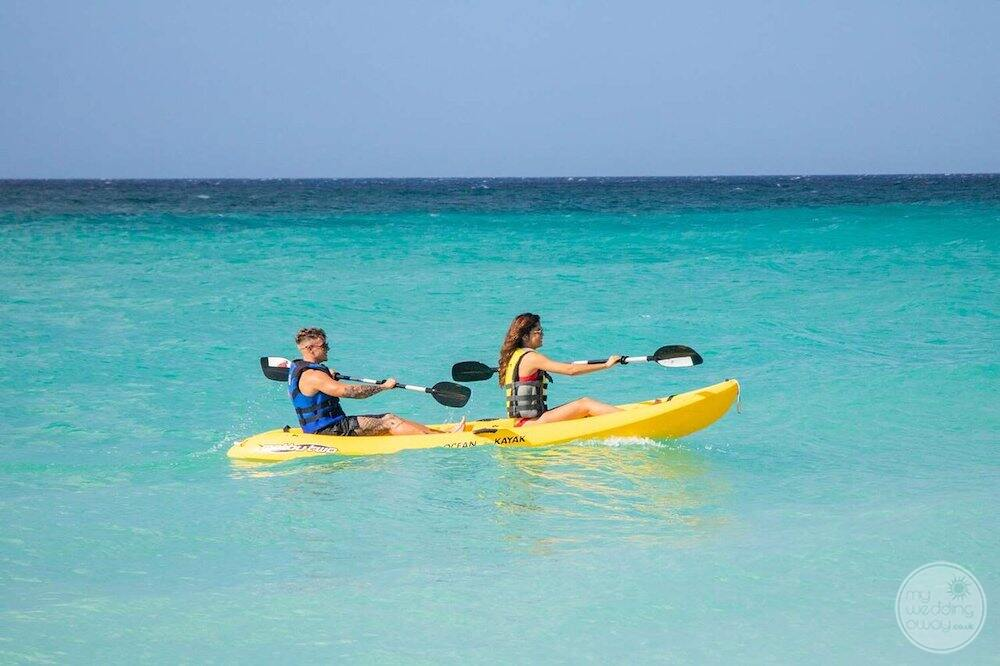 Guests in the ocean with kayaks paddling along the beach