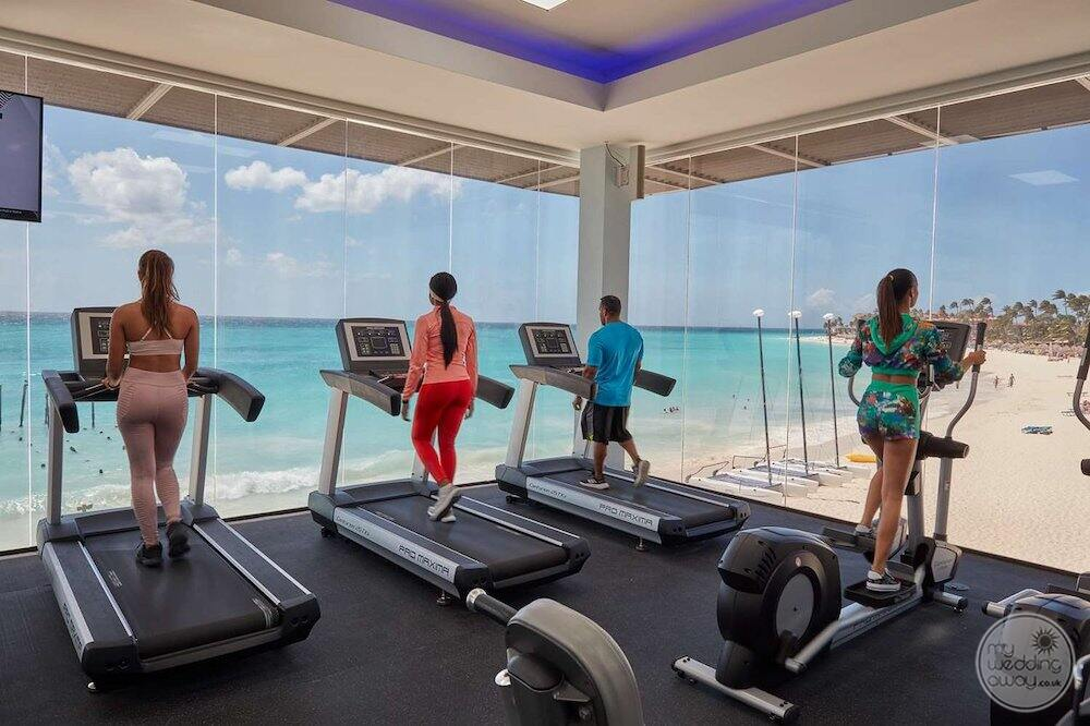 Oceanfront fitness centre with the guests running on the treadmill and in view of the ocean in the background